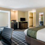King Bed End with Chair, Desk, Dresser, and TV at Quality Inn & Suites Albany